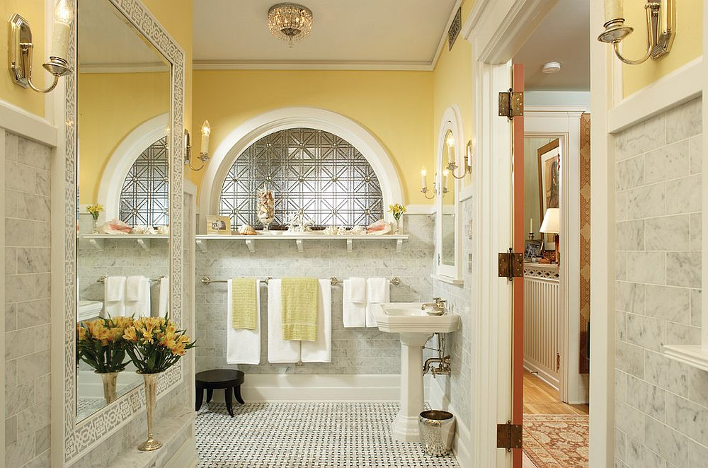 a lovely bathroom clad with grye marble tiles, yellow walls, an arched window, large mirrors and yellow towels