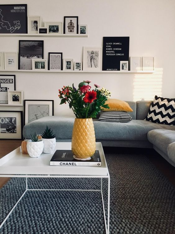 a lovely contemporary living room with neutral walls, a grey floor, a grey sofa, ledges with black and white artworks, yellow touches