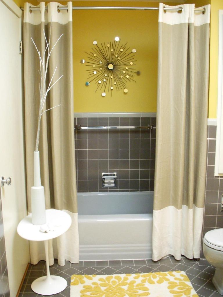 a mid-century modern bathroom with yellow walls, grye tiles, color block curtains, a floral rug and a sunburst decoration