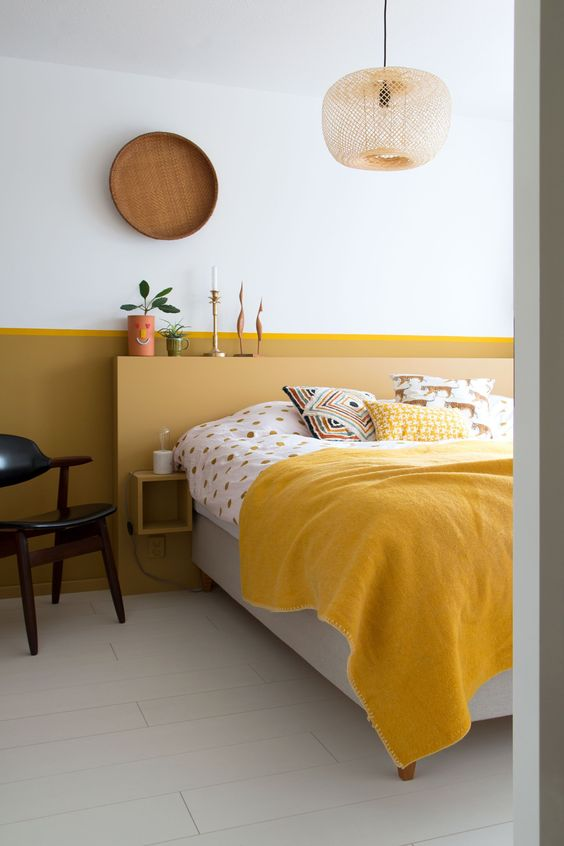 a mid century modern bedroom with a mustard color block wall, a mustard headboard and mustard and printed bedding plus a pendant lamp