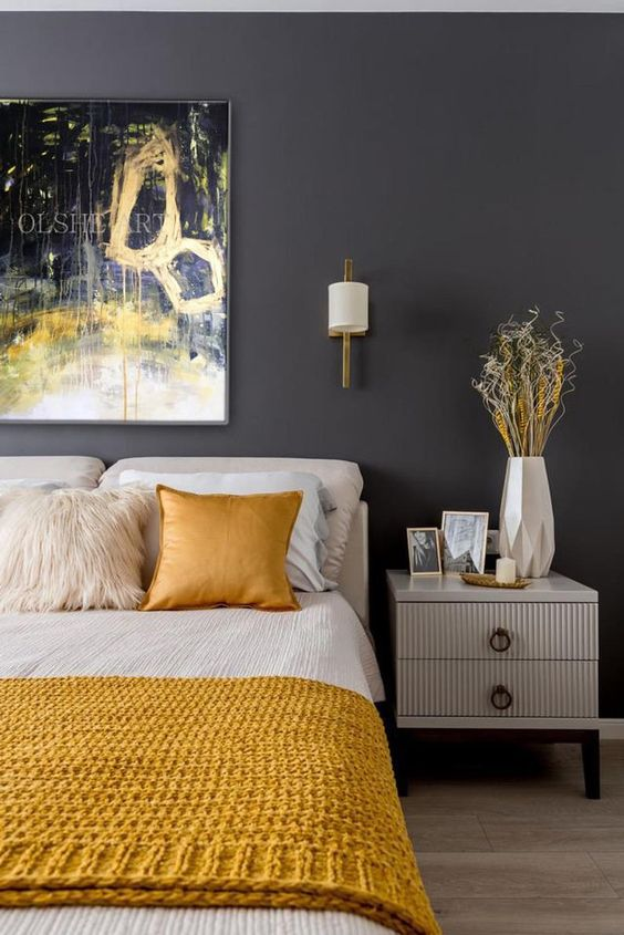 a mid-century modern bedroom with graphite grey walls, neutral furniture, a bold artwork, geometric decor and yellow bedding