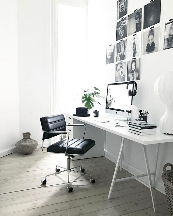 a minimal Scandinavian home office with a white desk, a black chair, a black and white gallery wall and basket is cool