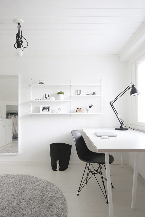 a minimal Scandinavian home office with a white desk, a black chair, a table lamp, a white hanging shelf