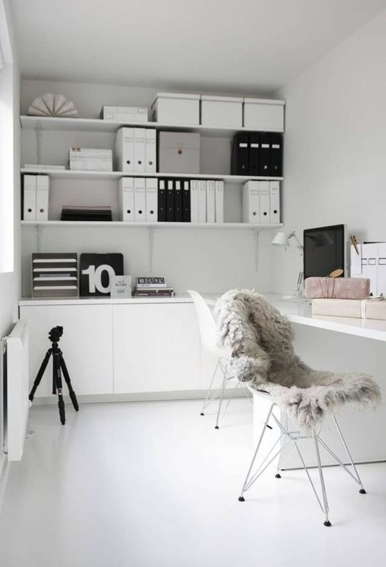 a minimalist Scandinavian home office with a white desk, some chairs, open shelving and several cabinets, with black touches