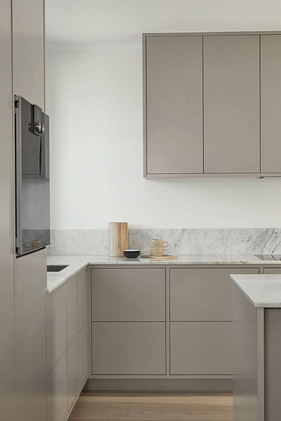 a minimalist Scandinavian kitchen with plain grey cabinets, white marble countertops and a backsplash is airy and serene