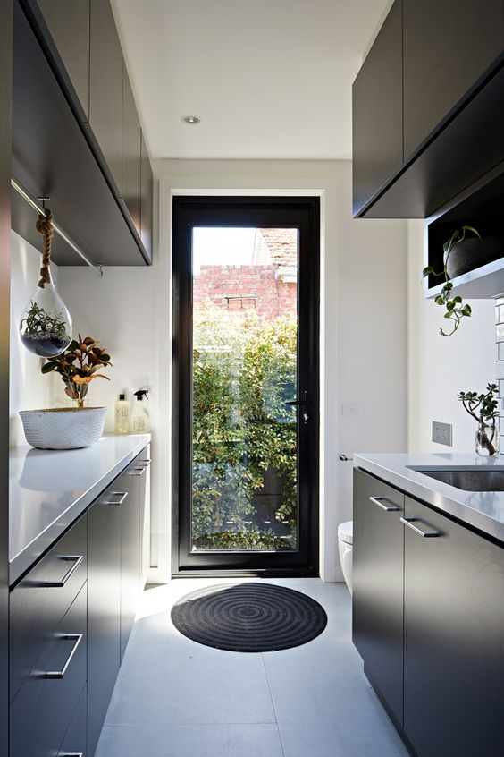 a minimalist black and white kitchen with suspended and usual potted plants, natural light coming through a door
