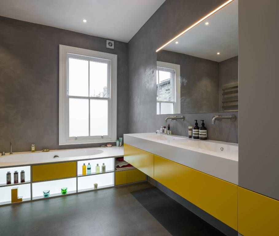 a minimalist gray and yellow bathroom done with concrete walls and a floor, a bathtub with lit up storage units, a yellow and grey vanity