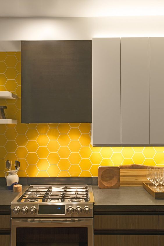 a minimalist kitchen with grey dove grey and wooden cabinets, a yellow hex tile backsplash and concrete countertops