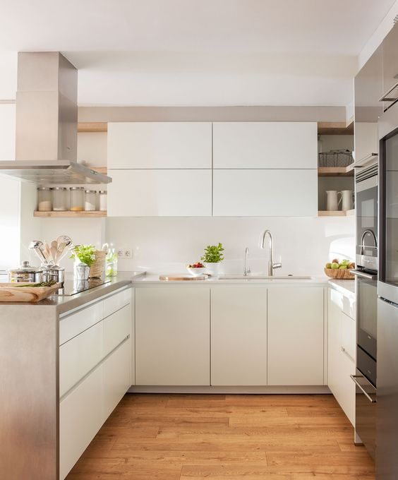 a minimalist white U-shaped kitchen with sleek cabinetry, stone and metal surfaces, elegant fixtures and stainless steel appliances