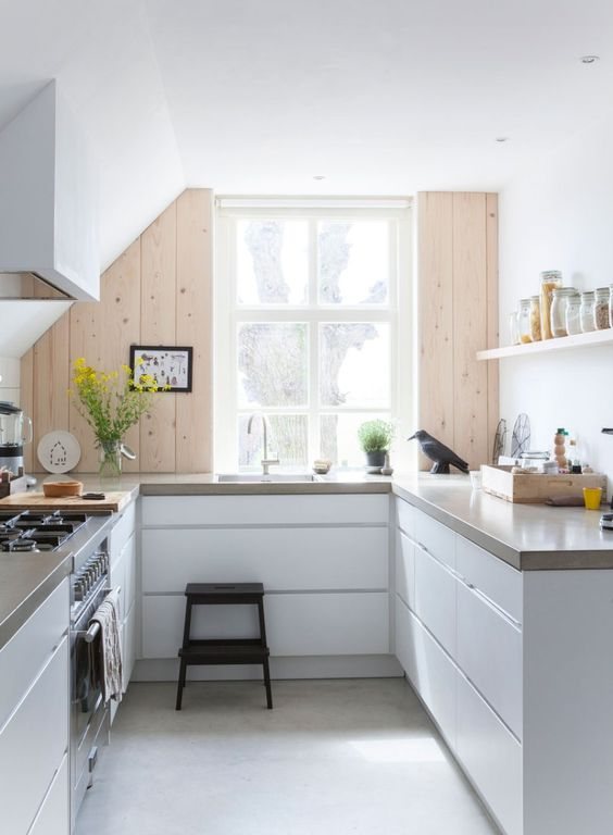 a minimalist white U-shaped kitchen with sleek cabinets, stone countertops, a wooden accent wall and bright yellow touches