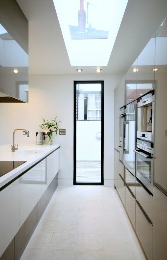 a minimalist white and tan kitchen with a skylight and a door to a balcony, shiny and sleek cabinets and lights