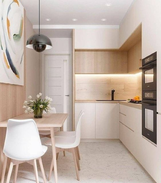 a minimalist white kitchen with a wooden backdrop and light stained wooden upper cabinets plus a dining space