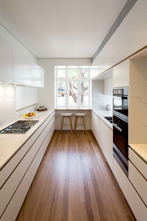 a minimalist white kitchen with marble backsplashes, some lights and a breakfast zone at the window is very cool