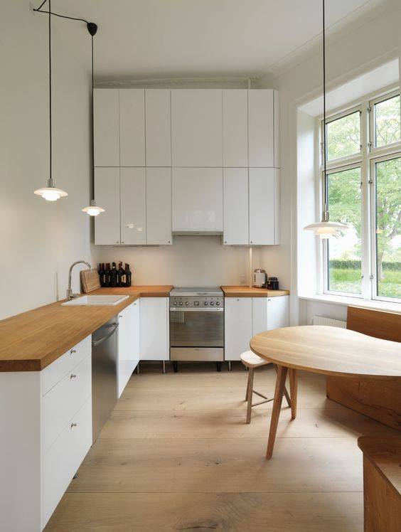 a minimalist white kitchen with wooden countertops, pendant lamps and a cozy eating area by the window