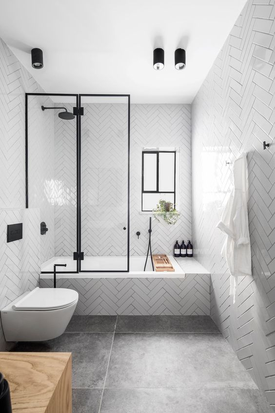 a modern Nordic bathroom clad with white herringbone tiles and large scale grey ones, with black fixtures for drama