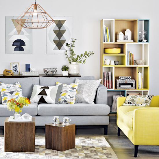 a modern and airy living room with a grey sofa, a yellow chair, wooden ottomans, a color block storage unit and bold artworks