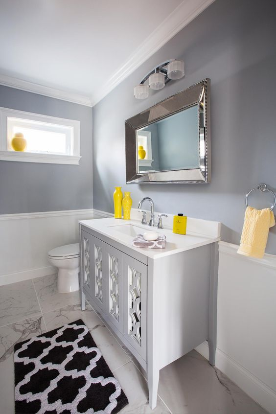 a modern grey and white bathroom with chic white vintage furniture and bold yellow touches and accents is very chic