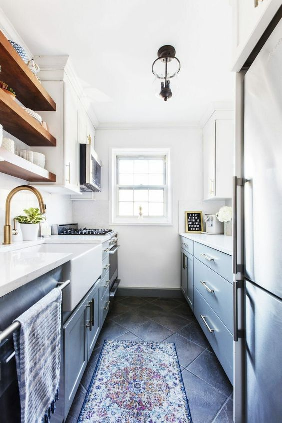 a modern grey and white galley kitchen with open wooden shelves, brass and stainless steel and a boho rug looks cool