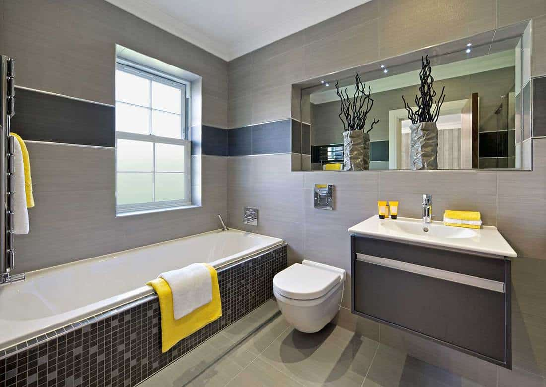 a modern grey bathroom with a tile clad tub, a dark grey vanity, white appliances and yellow touches