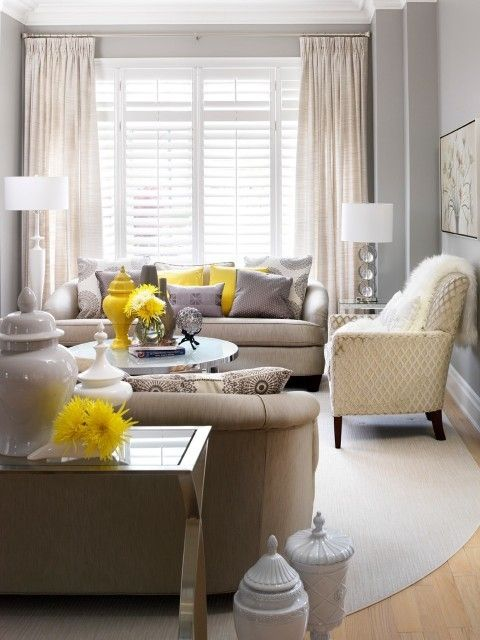 a modern living room with grey sofas, a printed chair, a mirror table, grey and yellow pillows and chic lamps