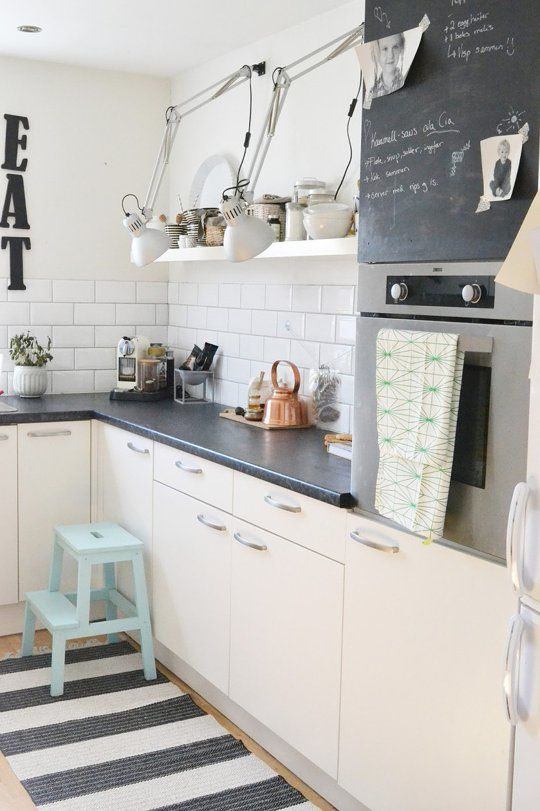 a modern monochromatic kitchen with warm colored cabinets, black countertops, a white subway tile backsplash and black touches