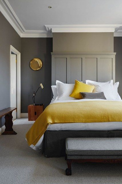 a moody bedroom with graphite grey walls, a grey paneled wall, heavy furniture, yellow and white bedding