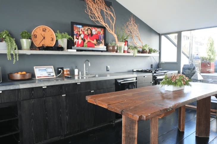 a moody one wall kitchen with black cabinets, a grey wall and a matching shelf and countertops, potted greenery and blooms and a wooden table