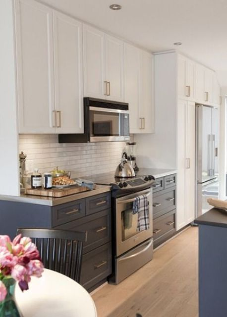 a navy and white galley kitchen with metal countertops and metal touches is very elegant and stylish