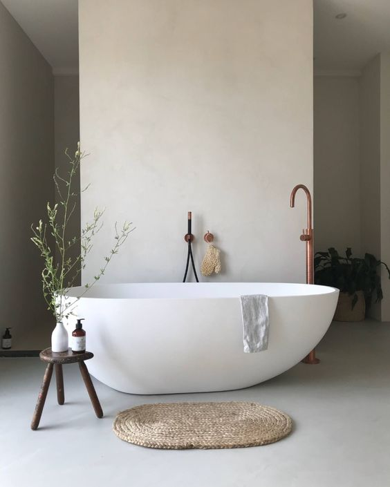 a neutral Nordic bathroom with light grey walls and a floor, an irregular shape tub, copper fixtures and wooden furniture