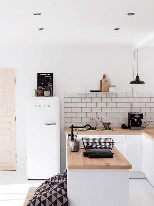 a neutral Scandinavian U-shaped kitchen with sleek white cabinetry, butcherblock countertops, a white subway tile backsplash and black fixtures