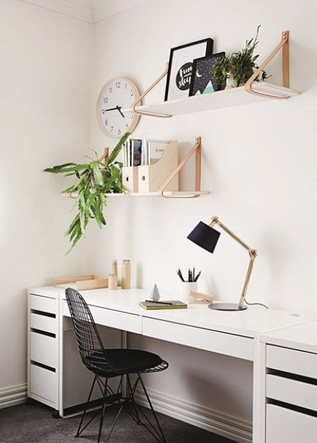 a neutral Scandinavian home office with a large desk, some suspended shelves, potted plants and a black metal chair