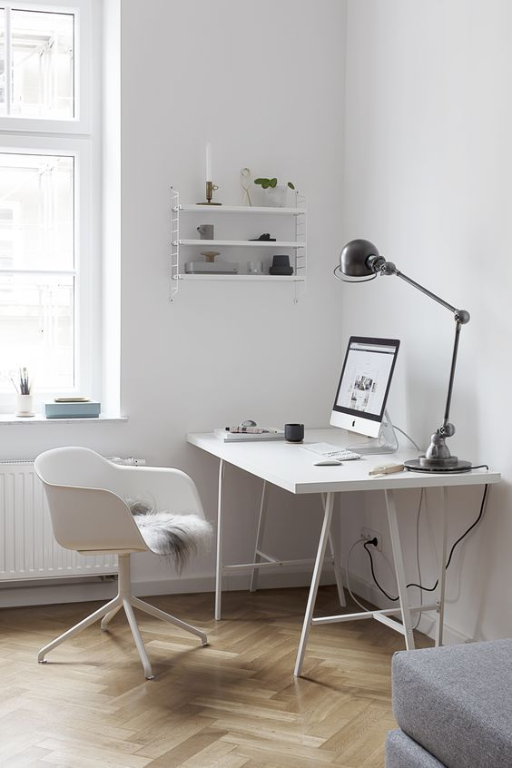a neutral Scandinavian home office with a white desk and a chair, a small white shelf on the wall and a vintage table lamp