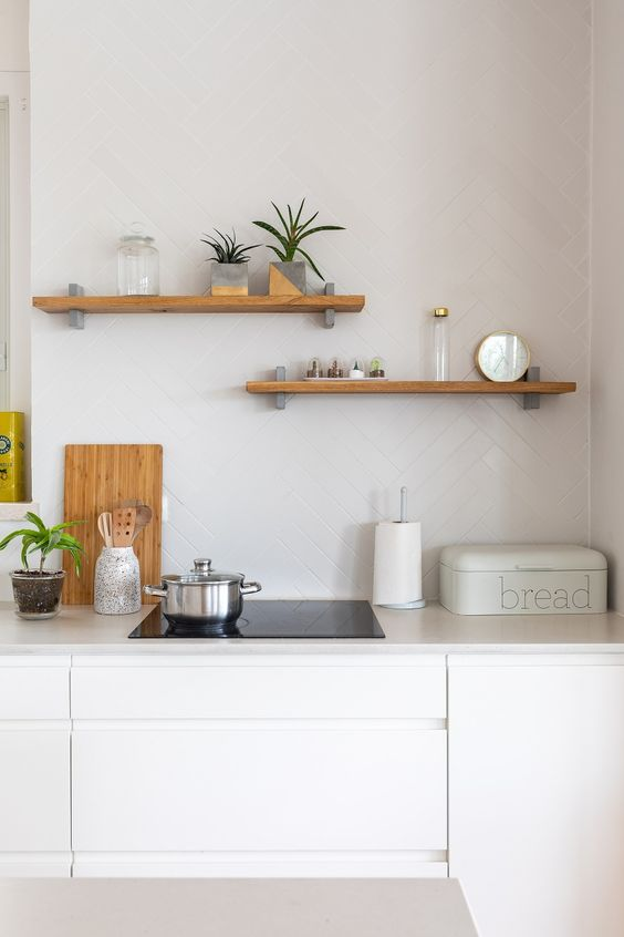 a neutral Scandinavian kitchen with sleek white cabinetry with whiet stone countertops, a white herrignbone backsplash and wooden shelves