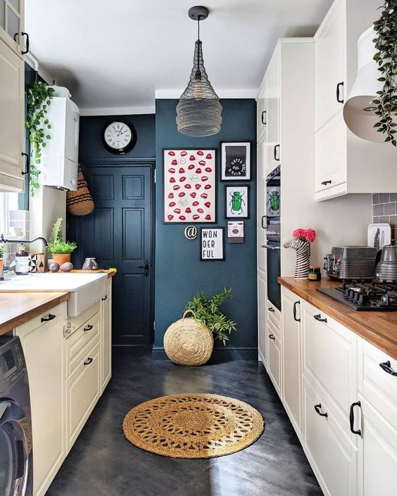 a neutral kitchen with navy walls, a pendant lamp, potted greenery, wooden countertops and a bright gallery wall