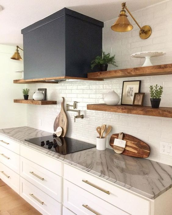 a neutral one wall kitchen with a grey stone countertop, stained open shelves, a white tile backsplash and a black hood plus gold sconces