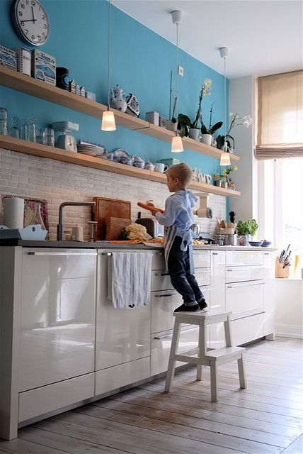 a pretty one wall kitchen with blue walls, plain white cabinets, open shelves and concrete countertops plus pendant lamps