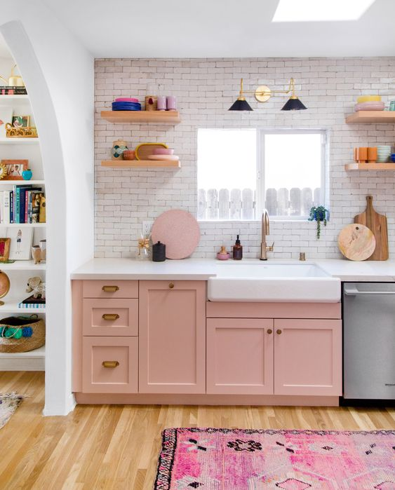 a pretty pink one wall kitchen with white countertops, open shelves, pastel tableware and a bold printed rug in pink