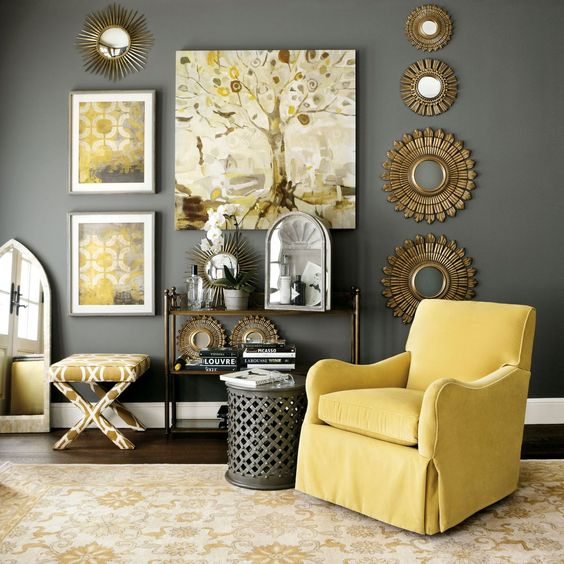 a rather dark grey wall and a side table, sunny yellow armchair, artworks and a printed chair for a trending space