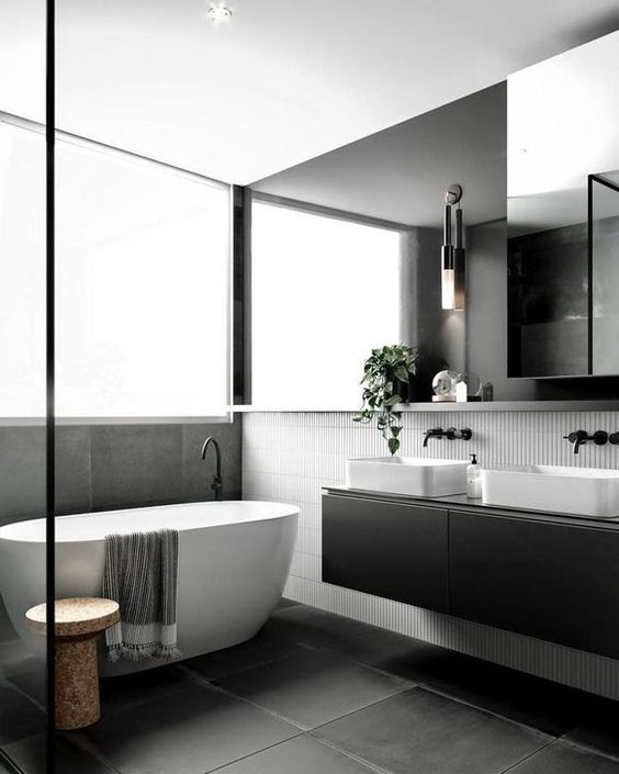 a refined Scandinavian bathroom with skinny white and large scale black tiles, a black double vanity, an oversized mirror and a cork stool by the tub