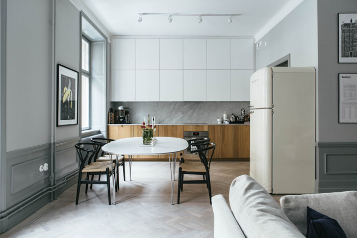 a refined Scandinavian kitchen with sleek white and wooden cabinets, a grey marble backsplash and a chic dining area