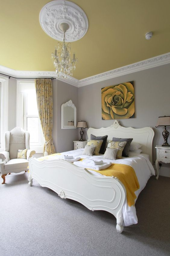 a refined bedroom with grey walls, refined creamy furniture, grey and mustard bedding, floral curtains, a mustard ceiling with a crystal chandelier