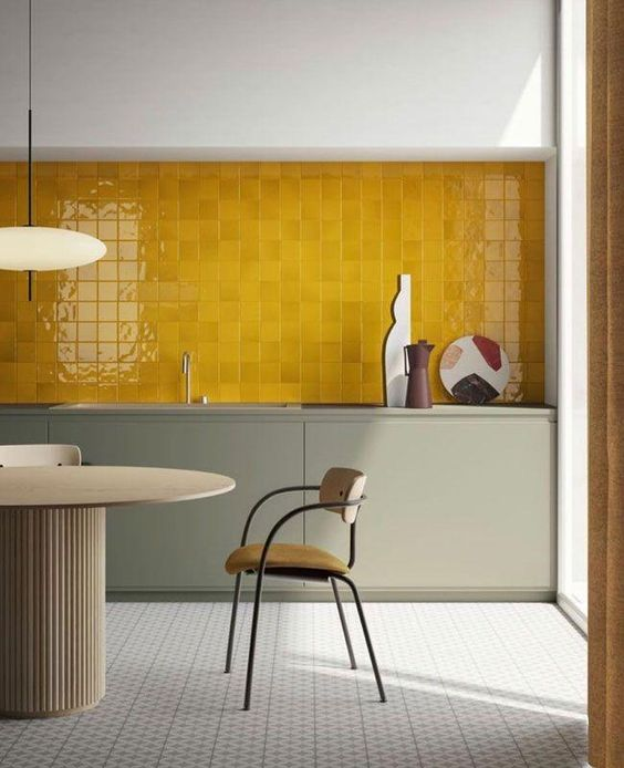 a refined kitchen with grey lower cabinets, a whole wall clad with juicy yellow tiles, elegant chairs and a table