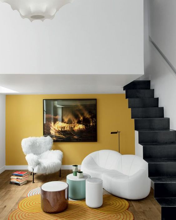 a refined living room nook with a mustard accent wall, a matching rug and beautiful sculptural furniture