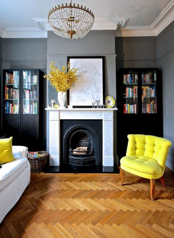 a refined living room with grey walls, black bookcases, a fireplace, a crystal chandelier, a white sofa and a lemon yellow chair