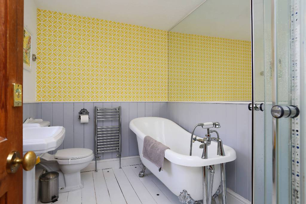 a refined vintage bathroom with grey beadboard and yellow wallpaper, vintahe white appliances and a large mirror
