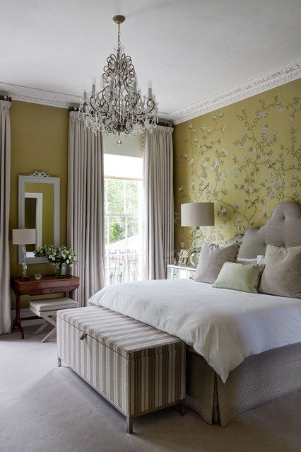 a refined vintage bedroom with mustard walls including a floral accent one, a dove grey bed and a striped bench, a crystal chandelier and dove grey curtains