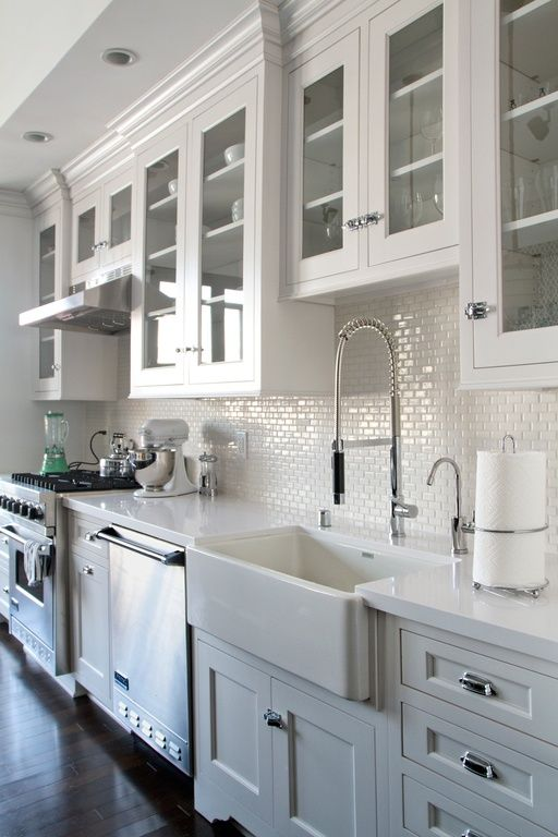 a refined white one wall kitchen with white tiles and stone countertops, stainless steel appliances and lights over the space