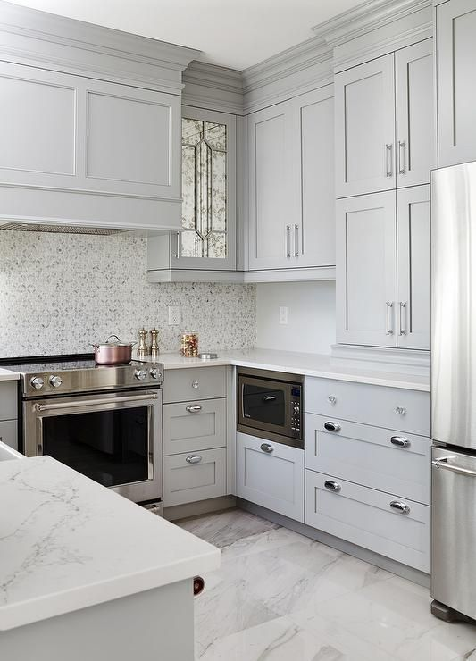 a relaxing and very refined grey U-shaped kitchen with a catchy backsplash. white stone countertops and stainless steel