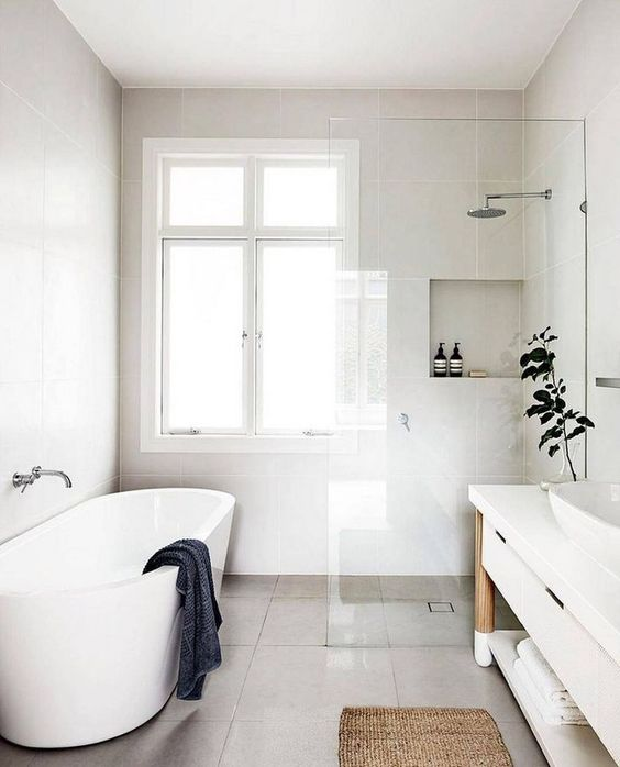 a serene Nordic bathroom with an oval tub, storage niches, a long vanity with a sink and potted greenery