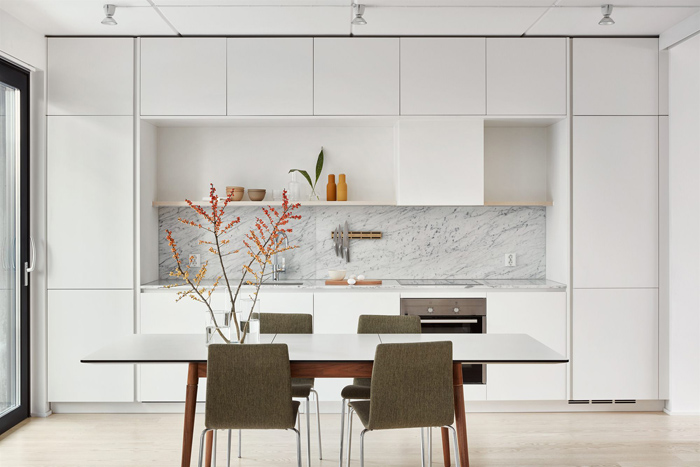 a serene Nordic kitchen with sleek white cabinetry, a white marble backsplash, a table and grey chairs for the eating zone